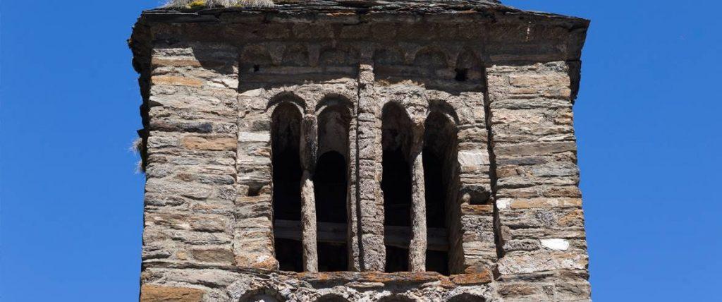 Sant Climent de Pal, también conocida en castellano como iglesia de San Clemente, es una auténtica joya del arte románico en Andorra. Está situada en Pal, en la parroquia de La Massana, y es una de las construcciones más antiguas que se pueden apreciar en el país. En su interior y en su exterior se conservan elementos de gran valor artístico, de finales del siglo XI y fechas posteriores. Además, los amantes de este estilo medieval pueden completar la visita de este templo con otra al Centro de Interpretación Andorra Románica, situado muy cerca de la iglesia. En esta página te ofrecemos la información que necesitas para conocer mejor ambos espacios de interés.  Sant Climent de Pal, una construcción histórica  Esta iglesia supone una construcción de importancia histórica, pues se considera uno de los templos más antiguos que se conservan actualmente en Andorra. Su edificación se remonta a finales del siglo XI o principios del siglo XII, aunque también ha experimentado modificaciones y ampliaciones en periodos más recientes. En cualquier caso, el conjunto arquitectónico conserva elementos muy singulares del proyecto original. Por ejemplo, su torre campanario, de estilo lombardo y tres alturas. Llaman la atención sus ventanas geminadas con arcos de medio punto, sobre todo las del último piso, pues son el único ejemplo de ventanas geminadas dobles en Andorra. Los muros de su nave, que es de planta rectangular, son en gran parte del periodo románico original.