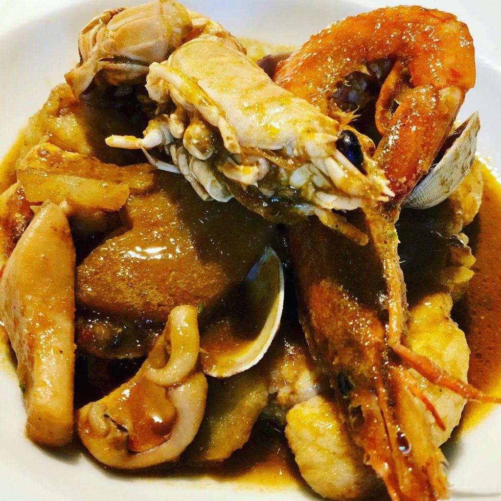 Un plat amb diferents tipus de peix i patates i molt típic de la costa catalana i també de les Balears, que era costum de fer pels pescadors, amb les restes de peix que els hi quedava sense vendre i malmés per les xarxes. Un plat deliciós pels amants dels plats de cullera. Aquest està fet amb rap però pot fer-se amb qualsevol altre tipus de peix de textura forta.  Què hi posem ?  1 cua de rap  Unes gambes fresques  Unes cloïsses  5 patates  1 ceba  2 tomàquets madurs  1 cullerada de pasta de nyora o pebrot xoricer  1 got de vi blanc del Penedès  Brou de peix  Oli d'oliva, sal i pebre  Per la picada:  2 alls  5 ametlles i 5 avellanes  1 cullerada de farina  julivert    Com ho fem ?  Rentarem bé el peix. Tallarem el rap a daus grossets, els salpebrerem i els marcarem en la cassola, amb oli d'oliva ben calent; farem el mateix amb les gambes; reservarem.  Obrirem les cloïsses al vapor, mirant de que no tinguin sorra i també les reservarem.  En el mateix oli farem el sofregit. Ratllarem la ceba i la sofregirem a foc lent. Un cop feta afegirem el tomàquet que haurem ratllat prèviament i la cullerada de pasta de nyora. Quan estigui ben fregit afegirem el got de vi i deixarem uns 5/6 minuts que redueixi.  Pelarem les patates i les tallarem escapçant-les; això farà que deixin el midó i la salsa quedi més espessa. Les incorporarem al sofregit i tot seguit afegirem el brou de peix, mirant de que cobreixi les patates. Deixarem bullir.  Quan faci uns 15 minuts que bullen les patates les provarem, segurament ja seran fetes, i afegirem el rap, les gambes i les cloïsses.  Farem la picada. Fregirem els alls en una miqueta d'oli. Un cop fregits els posarem en un morter i els xafarem amb les ametlles, les avellanes i el julivert. Agafarem una mica del brou i la cullerada de farina. Barrejarem tot bé al morter i abocarem la barreja a la cassola.  Deixarem uns 5 minuts més i ja el tindrem llest. Posarem per sobreuna mica de julivert trinxadet.