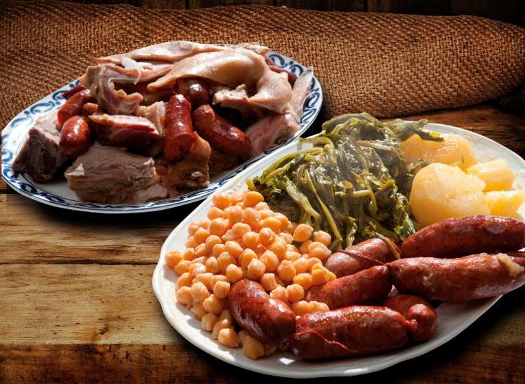 """Todos los viernes hasta final de invierno.  Te presentamos el plato estrella de Galicia en Borda Xixerella. Un delicioso cocido, hecho con los mejores ingredientes.  Ingredientes Garbanzos Grelos, berzas o repollo (a nuestra elección) ½ cachucha de Porco """"Cabeza de cerdo"""" ½ kg de patatas gallegas ½ lacón oreado 4 chorizos gallegos 1/2 costilla de cerdo ahumada  Agua Sal  Preparación  1.Lo primero que debemos de tener en cuenta es que tanto el lacón como la cachucha deberán estar en remojo durante un día y medio antes de hacer el cocido, cambiando un par de veces el agua.  Haremos lo mismo con los garbanzos, pero bastará con medio día de antelación.  2.En una olla de tamaño grande pondremos agua al fuego y cuando empiece a hervir añadiremos los garbanzos, la cachucha, el lacón y la costilla de cerdo ahumada..  En cuanto a los chorizos, hay quien también los añade en este paso o que los cuece aparte, os lo dejo a vuestra elección.  3.Dejaremos que cueza todo durante un par de horas aproximadamente y salaremos cuando lleve una hora al fuego.  4.Pasado este tiempo, retiraremos la carne a una fuente y la cortaremos a nuestro gusto.  5.En otra olla, coceremos el repollo o la verdura que hayamos escogido junto con las patatas enteras y los chorizos encima, en el caso de que queramos que vayan aparte. Pasados 20 minutos, sacaremos los chorizos y 10 minutos después la verdura y las patatas.  Presentacion  Podemos presentar nuestro cocido en fuentes diferentes: una para la carne y los chorizos y otra para la verdura, garbanzos y patatas.  ¡Estamos listos para este un gran manjar típico de Galicia!"""