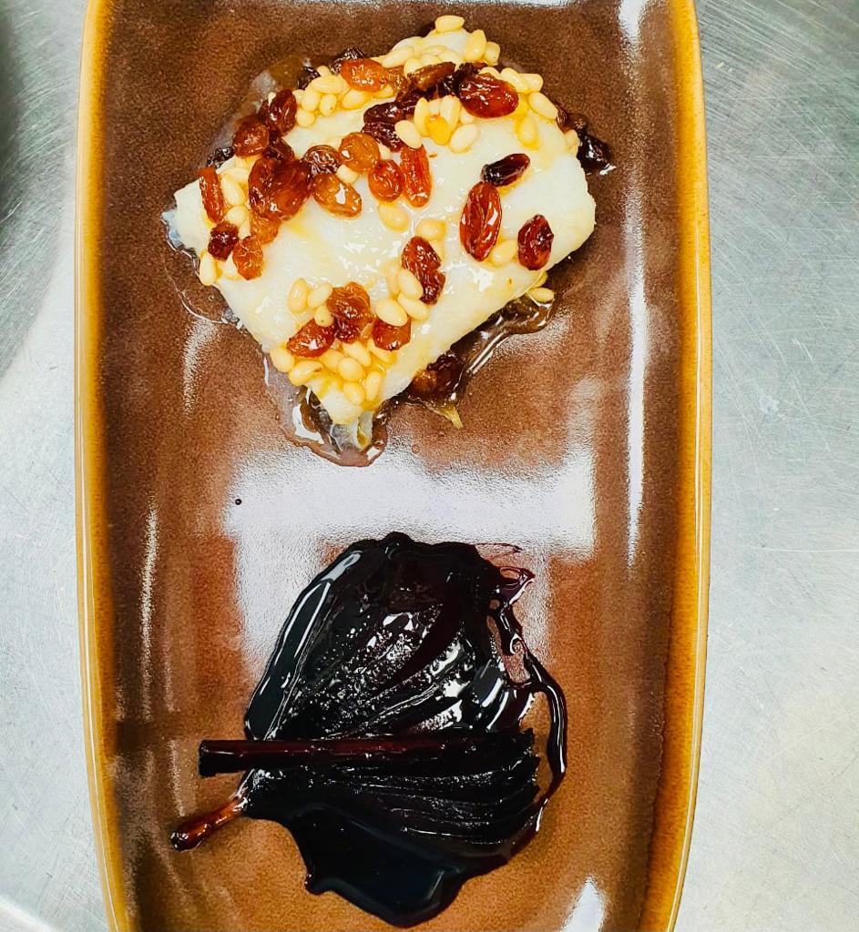 Bacallà amb mel amb salsa agredolça de mel, panses i pinyons sobre una base de ceba caramel·litzada